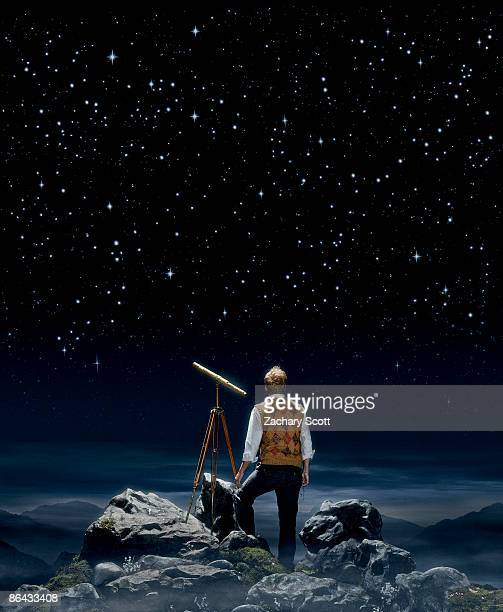 Man gazing at a night sky aside a telescope