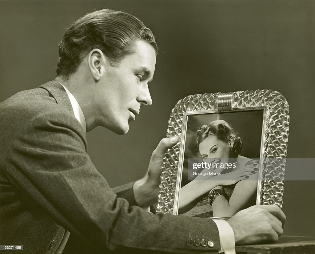 Man gazing at framed photo of woman : Stock Photo