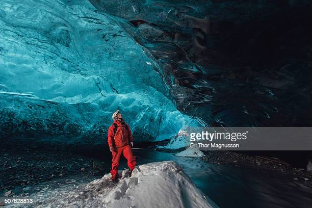 Man gazing upward in ice cave, Vatnajokull Glacier, Vatnajokull National Park, Iceland