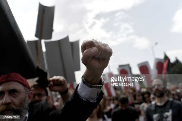 TOPSHOT A man gestures as he demonstrates with members of the Greek communist labour union in central Athens during the May Day celebrations on May 1...