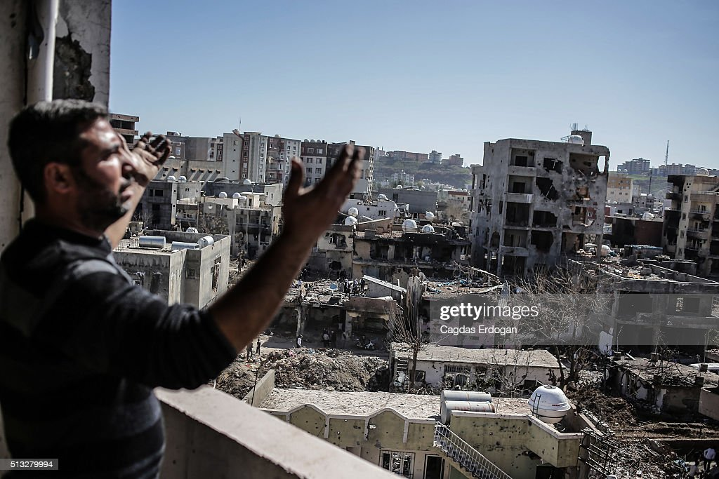 A man gestures as he looks to the ruined houses on March 2 2016 in Cizre Turkey Turkish authorities scaled down a 24hour curfew imposed on the mainly...