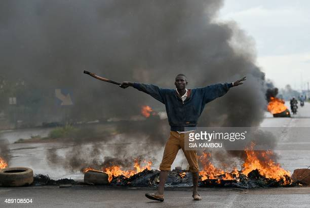 A man gestures as he stands in front of burning tires on September 19 2015 in Ouagadougou Burkina Faso's capital The protest comes several days after...