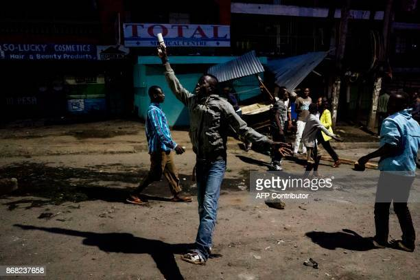 A man gestures as others take down a stand following the announcement of results of a presidential election rerun in Mathare slums in Nairobi on...