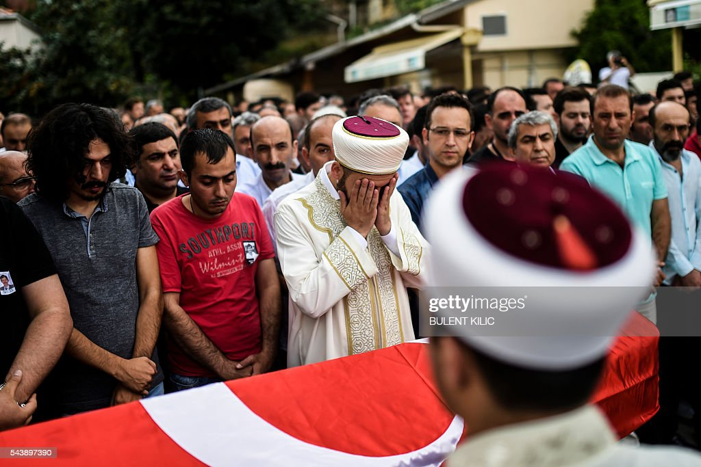 A man gestures as people gather in front of the coffin for the funeral of Turkish teacher Huseyin Tunc in Istanbul on June 30, 2016 two days after the triple suicide bombing and gun attack occurred at Istanbul's Ataturk airport. The death toll from the triple suicide bombing and gun attack that occurred on June 28, 2016 at Istanbul's Ataturk airport has risen to 43 including 19 foreigners. The government has pointed the finger of blame at the Islamic State group and Turkish police rounded up 13 suspected IS jihadists in raids at 16 different locations across Istanbul on June 30. / AFP / BULENT