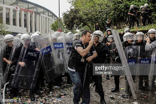 A man gestures as Turkish antiriot police use tear gas and water cannon to disperse supporters around the stadium before the Turkish Spor Toto Super...