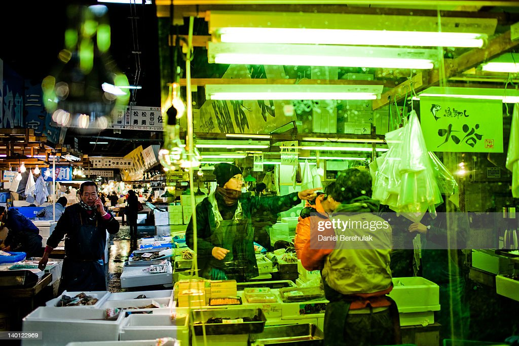 A man gestures for assistance as he and others work at the Tsukiji fish market on February 28 2012 in Tokyo Japan Handling nearly 3000 tons of fish a...
