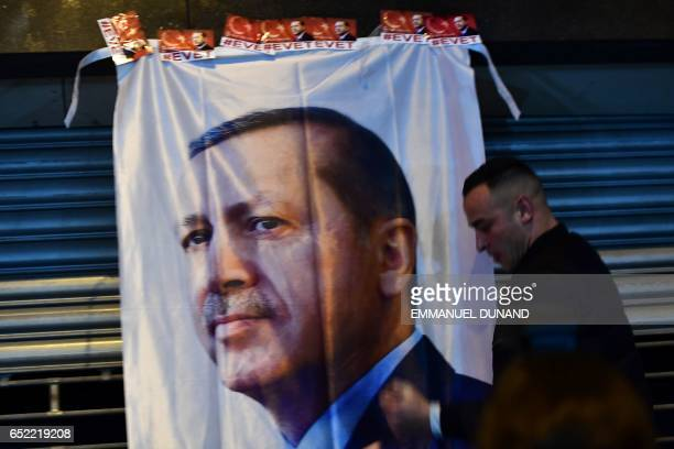 A man gestures in front of a flag bearing a portrait of Turkish President Recep Tayyip Erdogan as Turkish residents of the Netherlands gather for a...