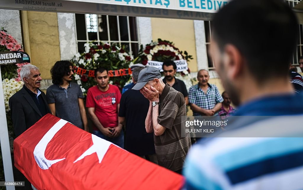 A man gestures in front of the coffin as people gather for the funeral of Turkish teacher Huseyin Tunc in Istanbul on June 30, 2016 two days after the triple suicide bombing and gun attack occurred at Istanbul's Ataturk airport. The death toll from the triple suicide bombing and gun attack that occurred on June 28, 2016 at Istanbul's Ataturk airport has risen to 43 including 19 foreigners. The government has pointed the finger of blame at the Islamic State group and Turkish police rounded up 13 suspected IS jihadists in raids at 16 different locations across Istanbul on June 30. / AFP / BULENT