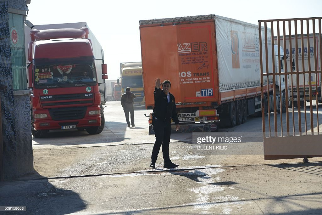 A man gestures on February 9, 2016 at the Turkish Oncupinar crossing gate between Turkey and Syria, near Kilis, where people wait for a truck to drive them back and forth. Around 30,000 Syrians are at the Turkish border after fleeing a Russia-backed regime offensive on the northern region of Aleppo, Turkish Prime Minister Ahmet Davutoglu said on February 8, as his country faces mounting pressure to open its border. Davutoglu said the refugees would be admitted if need be, although Turkey should not be expected 'to shoulder the refugee issue alone.'. / AFP / BULENT KILIC