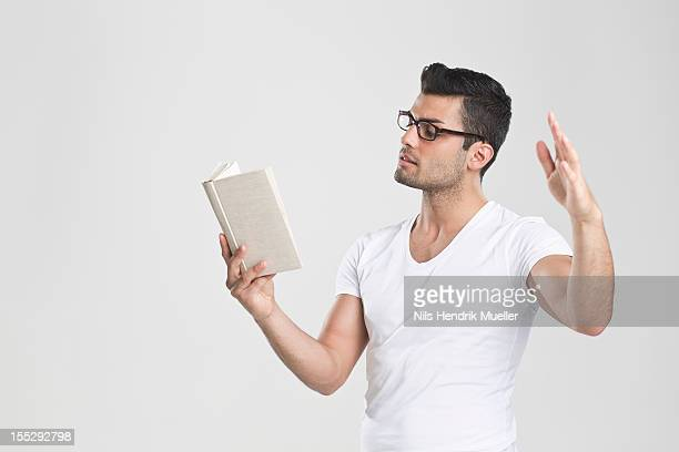 Man gesturing and reading book