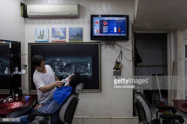 A man gets a shave at a barbers shop while coverage of the referendum results play on a tv on April 16 2017 in Istanbul Turkey According to...