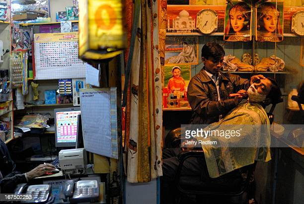 A man gets a shave in a cramped cabin while next door a man plays a lotter game while waiting for customers to use his phones in a small shopping...