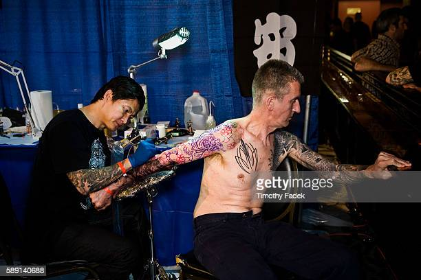 A man gets a tattoo at the 12th Annual New York City Tattoo Convention at Roseland Ballroom in Manhattan