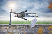 Man flying away horizontally in a storm while holding on to a street lamp with one hand. The other hand is holding an upended umbrella.
