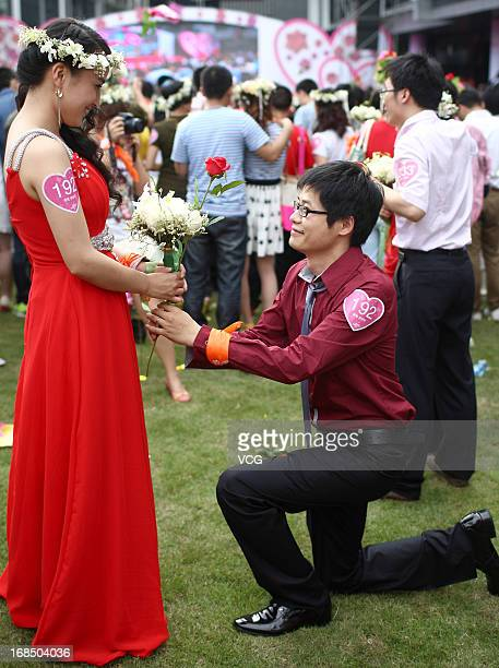 A man gets down on one knee to propose marriage to his girlfriend during a group wedding ceremony with 688 newlywed couples participating at Alibaba...