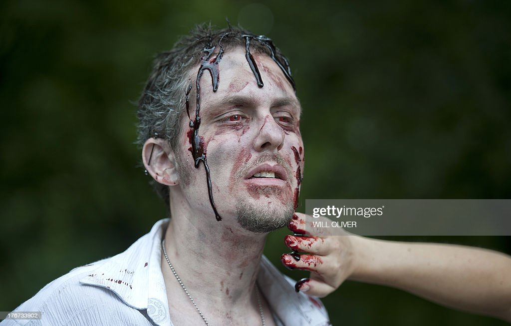 A man gets fake blood applied to look like a zombie during a 'Zombie training day' in Hyde Park, Central London, on August 18, 2013. Participants were offered some training and put through a range of activities in preparation for the Zombie Evacuation Race events in various UK cities in October.