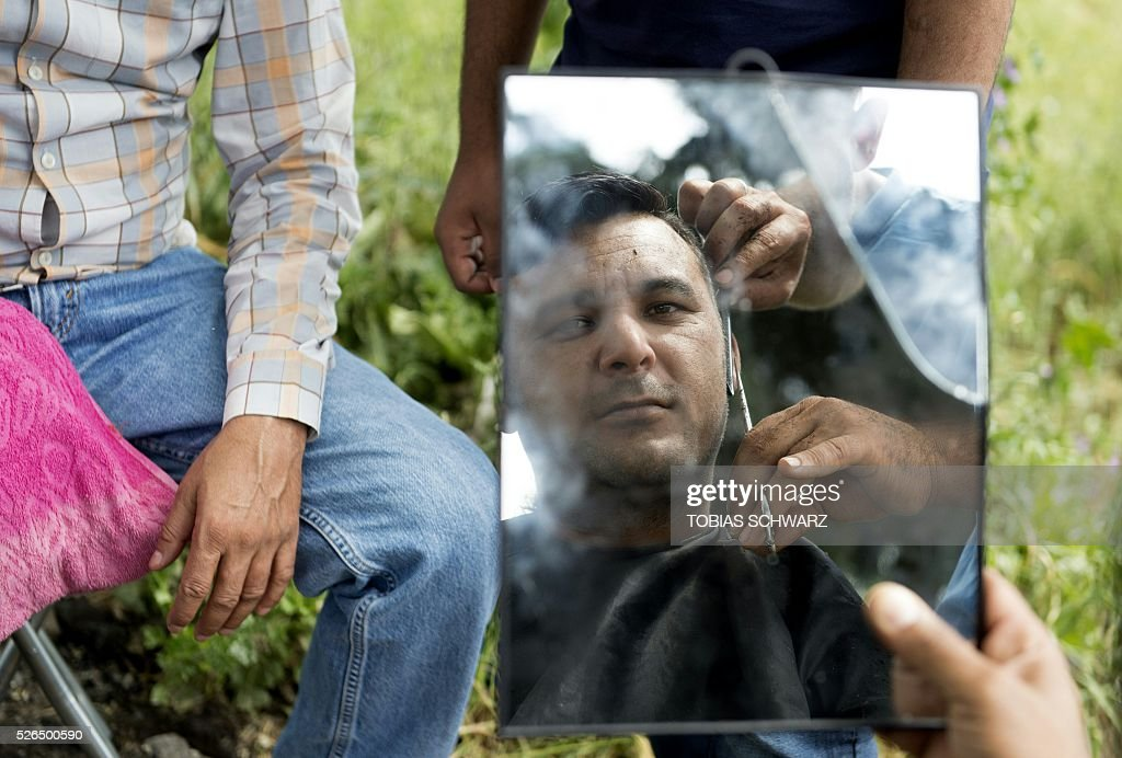 A man gets his hair dressed as he holds a mirror at a makeshift camp for migrants and refugees near the village of Idomeni not far from the Greek-Macedonian border on April 30, 2016. Some 54,000 people, many of them fleeing the war in Syria, have been stranded on Greek territory since the closure of the migrant route through the Balkans in February. / AFP / TOBIAS