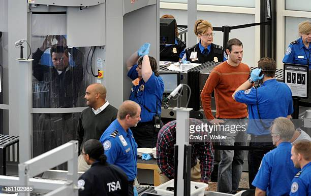A man gets instruction from a Transportation Security Administration agent while passing through a full body scanner at Denver International Airport...