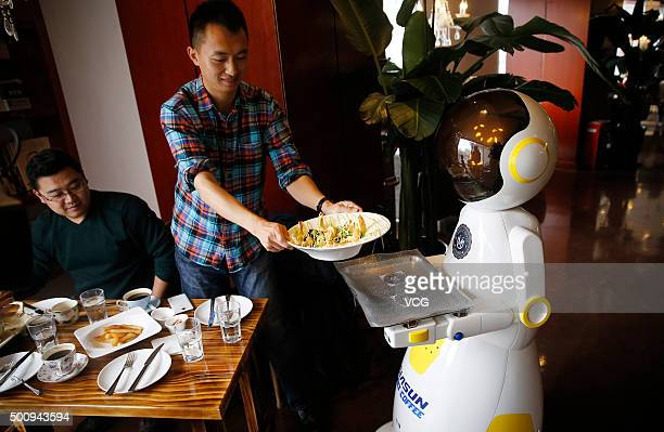 A man gets meals from a robot delivering meals at a western restaurant on December 11 2015 in Qingdao Shandong Province of China It's said that the...