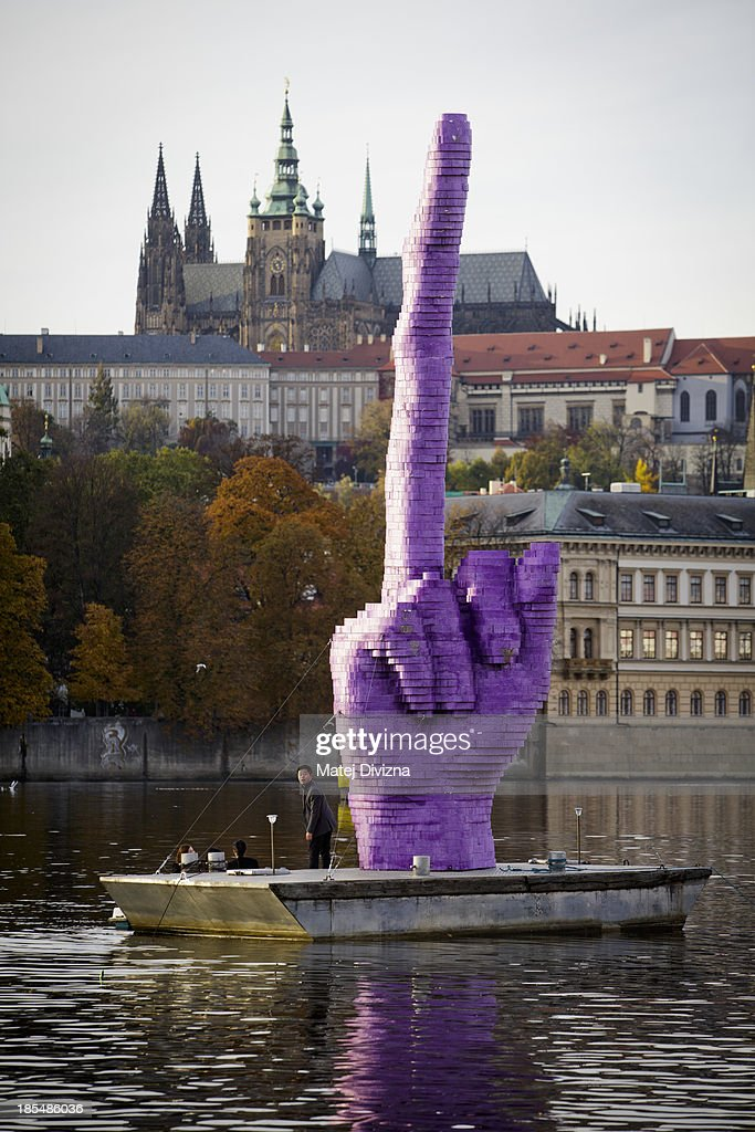A man gets out of his pedal boat and stands on the base where the sculpture 'Middle Finger ' by David Cerny stands pointing towards Prague Castle, the seat of the Czech President Milos Zeman, on the Moldau river on October 21, 2013 in Prague, Czech Republic.