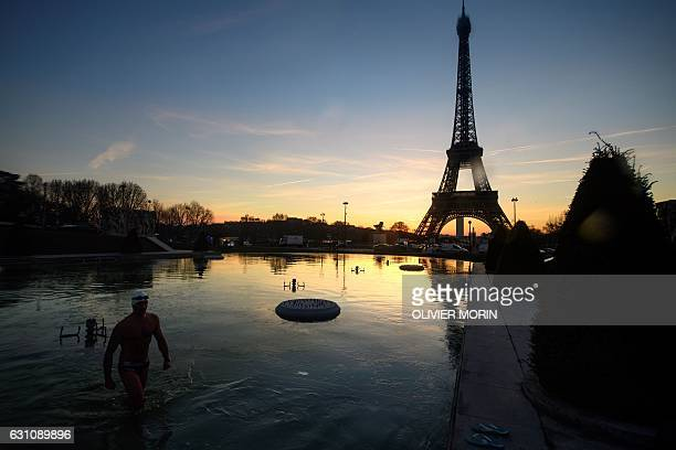TOPSHOT A man gets out of the frozen water of the Trocadero fountain in front of the Eiffel Tower in Paris early on January 6 2017 / AFP / OLIVIER...
