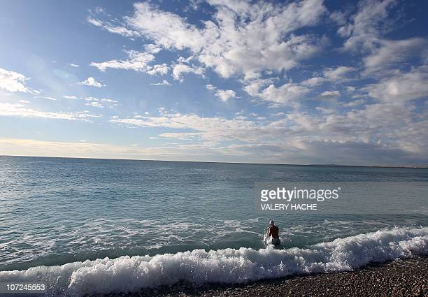A man gets ready to swim in the mediterranean sea under a sunny sky on November 27 2010 in Nice southeastern France AFP PHOTO VALERY HACHE