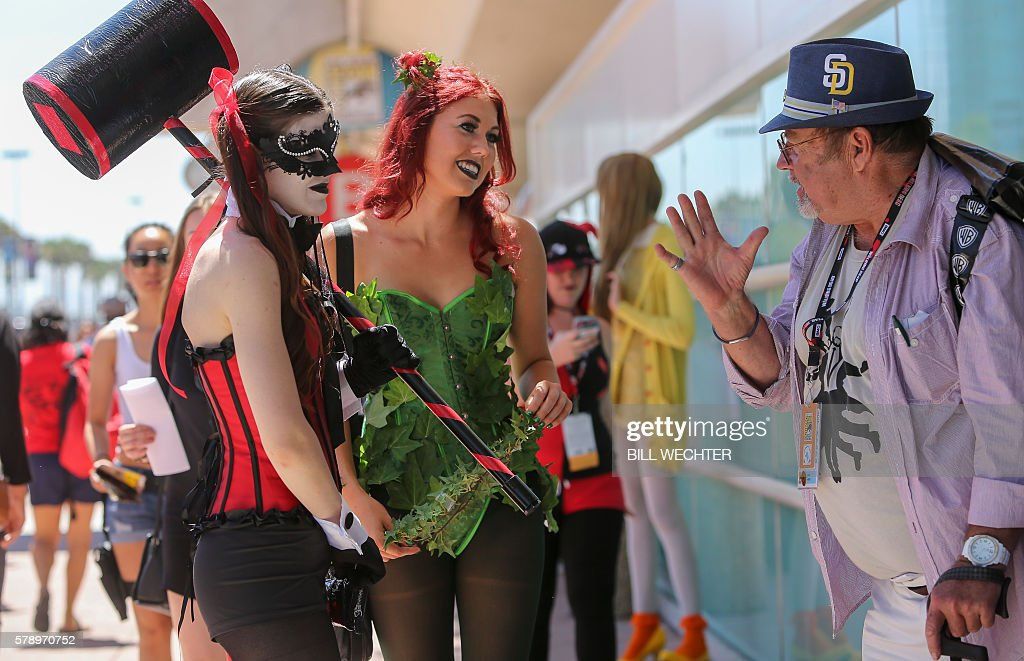 A man gets some advice from chracters Harley Quinn, left, and Poison Ivy, both from the Batman series, during Comic-Con International 2016 in San Diego, California, July 22, 2016. / AFP / Bill Wechter