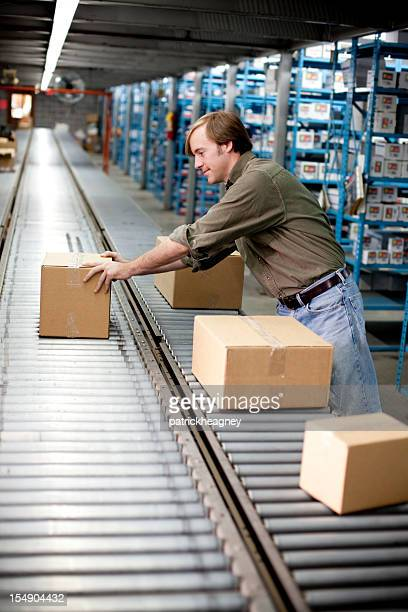 Man getting a box off of conveyer belt
