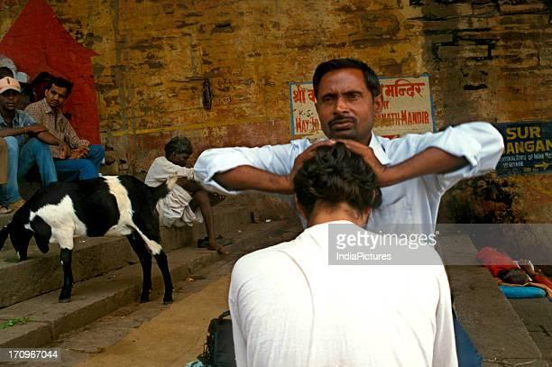 Man getting a massage at a ghat in Varanasi Uttar Pradesh India