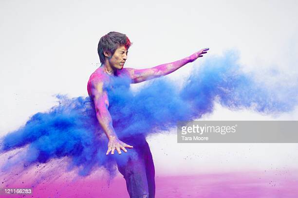 man getting blasted with blue powder