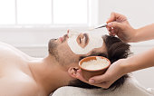 Unshaven man getting facial nourishing mask by beautician at spa salon