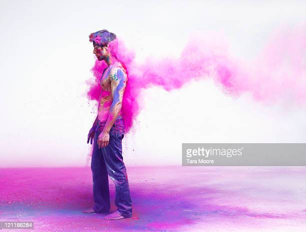 man getting impacted by pink powder paint