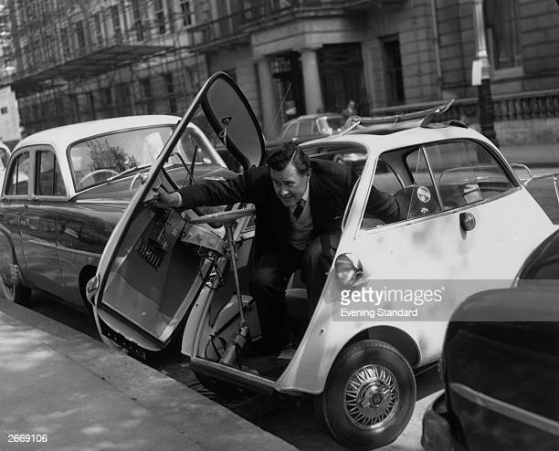 A man getting out of a neatly parked BMW Isetta by using the door at the front of the car