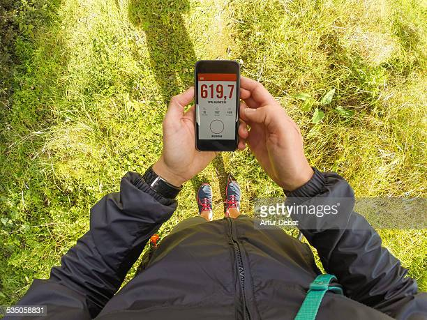 Man getting ready to run checking the running application on his smartphone from personal point of view
