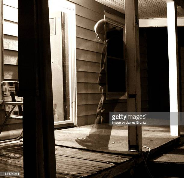 Man  ghostly   stands on   porch