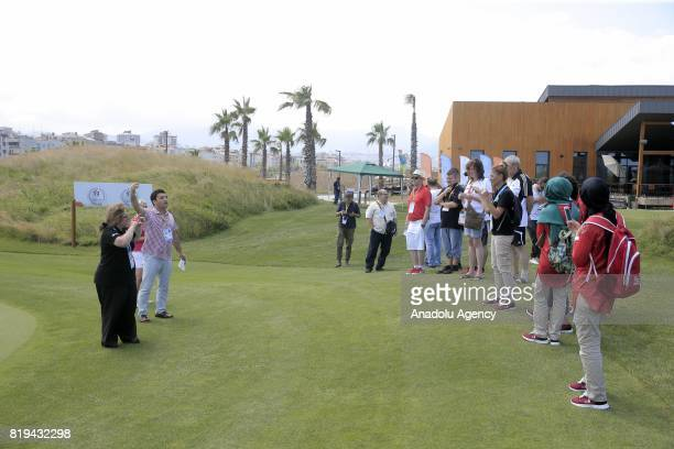 A man gives a briefing as a woman speaks in sign language on a golf field during a meeting for Turkish and foreign media members ahead of the golf...