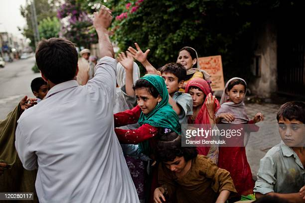 A man gives a free hand out of Naan bread to families at 'Iftar' when Muslims break their fast on the second day of the holy month of Ramadan on...
