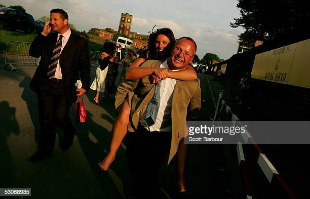 A man gives a lady race goer a piggy back ride home after attending the third day Ladies Day of Royal Ascot 2005 at York Racecourse on June 16 2005...