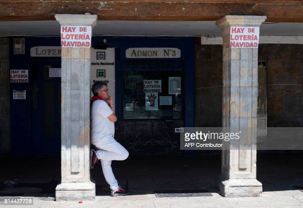 A man gives a phone call as he leans on a column during the last day of the San Fermin festival in Pamplona northern Spain on July 14 2017 The...
