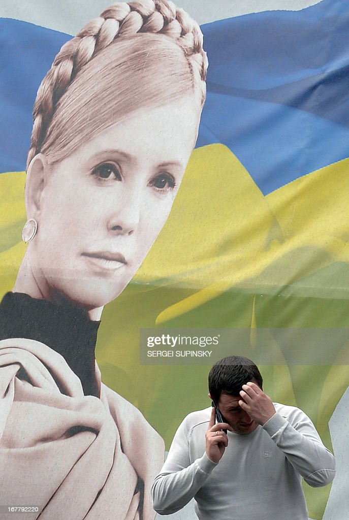 A man gives a phone call in front of a portrait of jailed former Ukrainian prime minister and the leader of the opposition Yulia Tymoshenko in the center of Kiev on April 30, 2013. The European Court of Human Rights on Tuesday ruled that Ukraine's detention of Yulia Tymoshenko was unlawful but threw out accusations of ill-treatment. 'The Court considered that the detention had been arbitrary and unlawful during the entire period,' the judges of the Strasbourg-based court said. AFP PHOTO/ SERGEI SUPINSKY