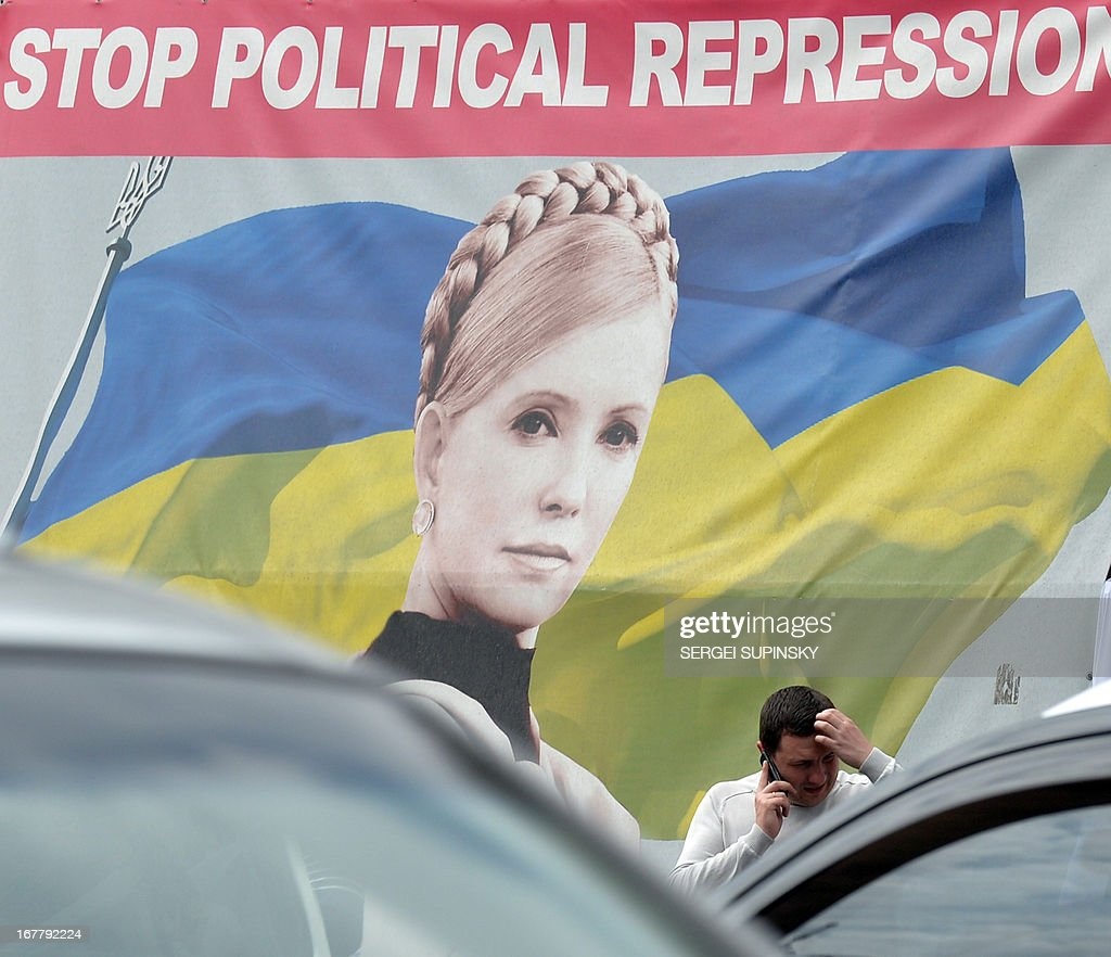 A man gives a phone call in front of a portrait of jailed former Ukrainian prime minister and the leader of the opposition Yulia Tymoshenko in the center of Kiev on April 30, 2013. The European Court of Human Rights on Tuesday ruled that Ukraine's detention of Yulia Tymoshenko was unlawful but threw out accusations of ill-treatment. 'The Court considered that the detention had been arbitrary and unlawful during the entire period,' the judges of the Strasbourg-based court said.
