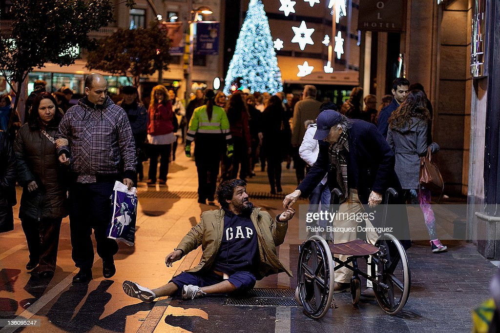 A man gives alms to a dissable man begging near Plaza Callao six days before Christmas Day on December 19, 2011 in Madrid, Spain. This year businesses are starting sales and discounts before Christmas to try and gain customers during the current economic crisis.
