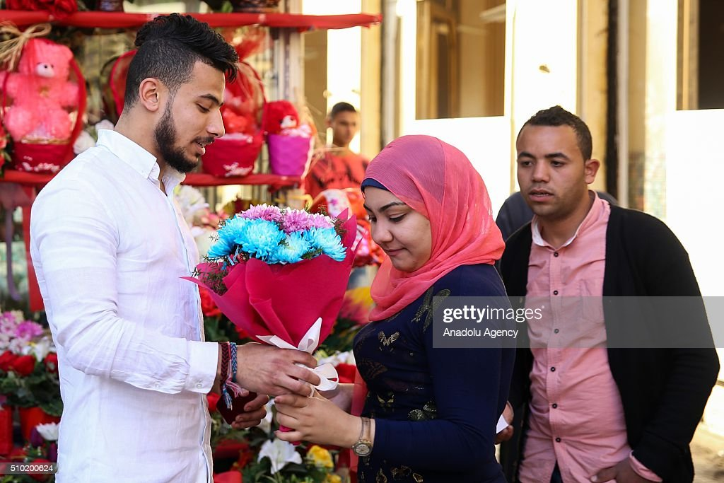 A man gives flowers a woman in front of a flower market during Valentine's Day in Cairo, Egypt on February 14, 2016.