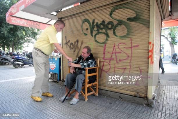 A man gives money to a beggar next to a closing kiosk in Thessaloniki on 9 September 2011AFP PHOTO/Sakis Mitrolidis