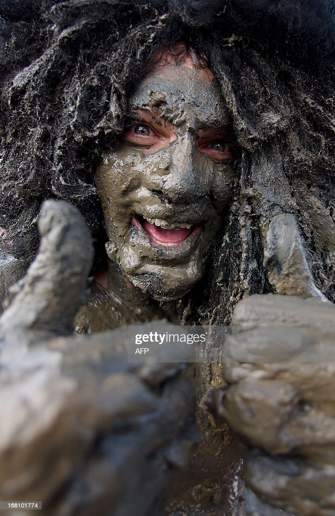 A man gives the thumbs up as he recovers at the end of the annual Maldon Mud Race in Maldon, Essex on May 5, 2013. The race sees people running on a short course across a muddy estuary in fancy dress to raise money for charities. The bank holiday weekend has seen one of the longest stretches of hot weather in England so far this year. AFP PHOTO/Leon Neal