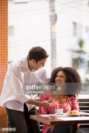 Man gives woman flowers upon arrival at restaurant : Stock Photo