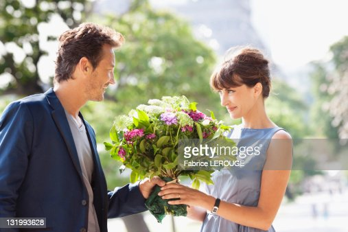 Man giving a bouquet of flowers to a woman with the Eiffel Tower in the background, Paris, Ile-de-France, France : Stock Photo