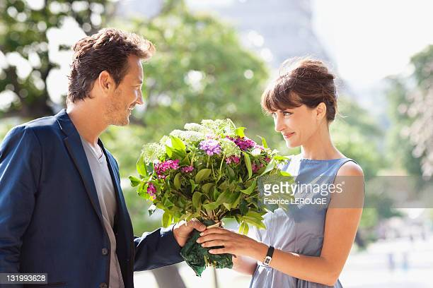 Man giving a bouquet of flowers to a woman with the Eiffel Tower in the background, Paris, Ile-de-France, France