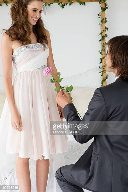Man giving a flower to a woman in the bedroom