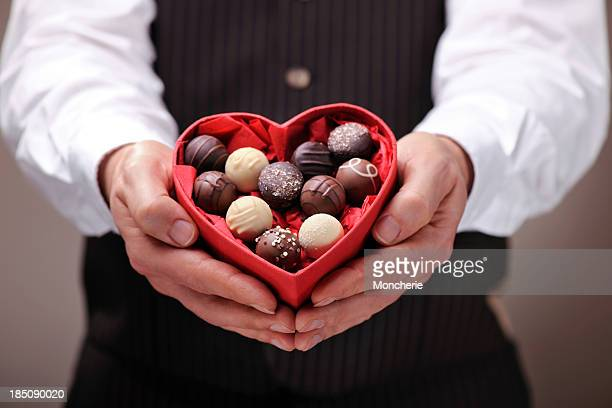 Man giving a heart shaped chocolate praline box